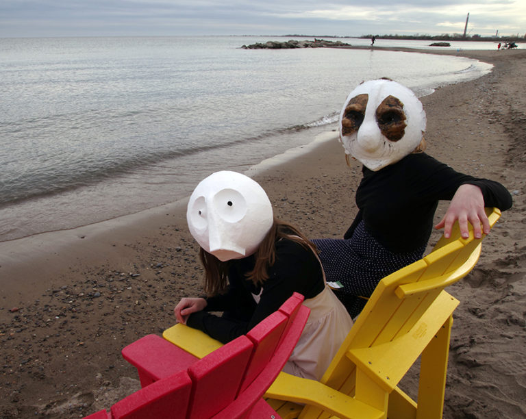 Animacy Theatre Collective's Morgan Johnson and Alexandra Siimpson in papier mache masks at Toronto Waterfront. Photography by Kathryn Hanson, ShutteredEye Photography.